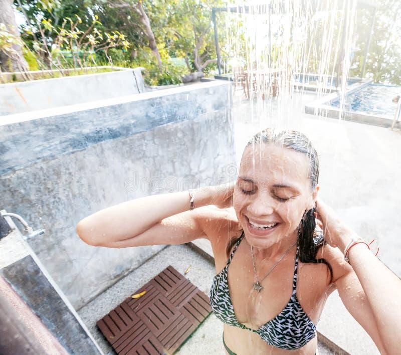 Giovane bella donna sorridente felice che prende un'aria aperta della doccia, af fotografia stock