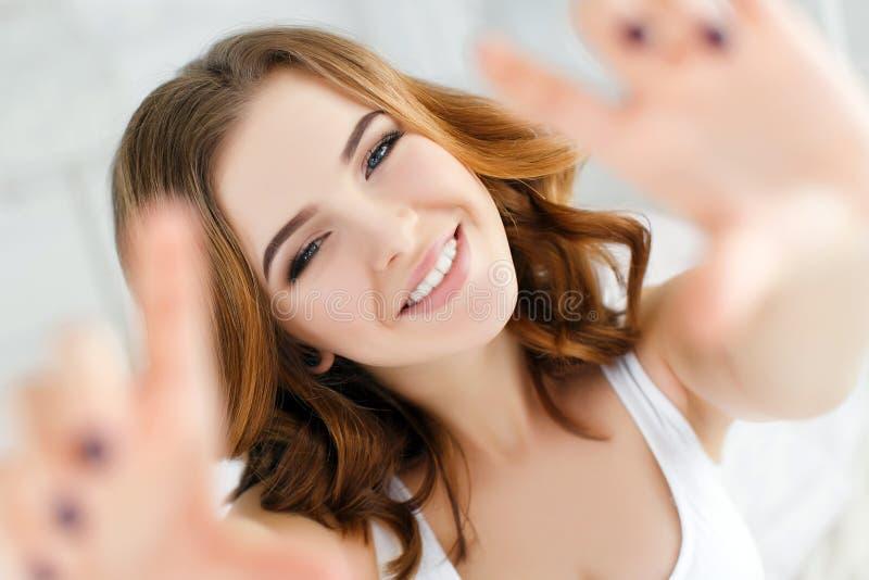 Giovane bella donna sorridente felice che sveglia sul letto immagine stock libera da diritti