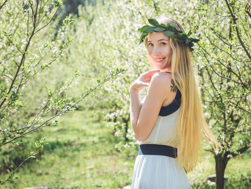 Giovane bella donna sorridente negli alberi del fiore di primavera immagine stock libera da diritti