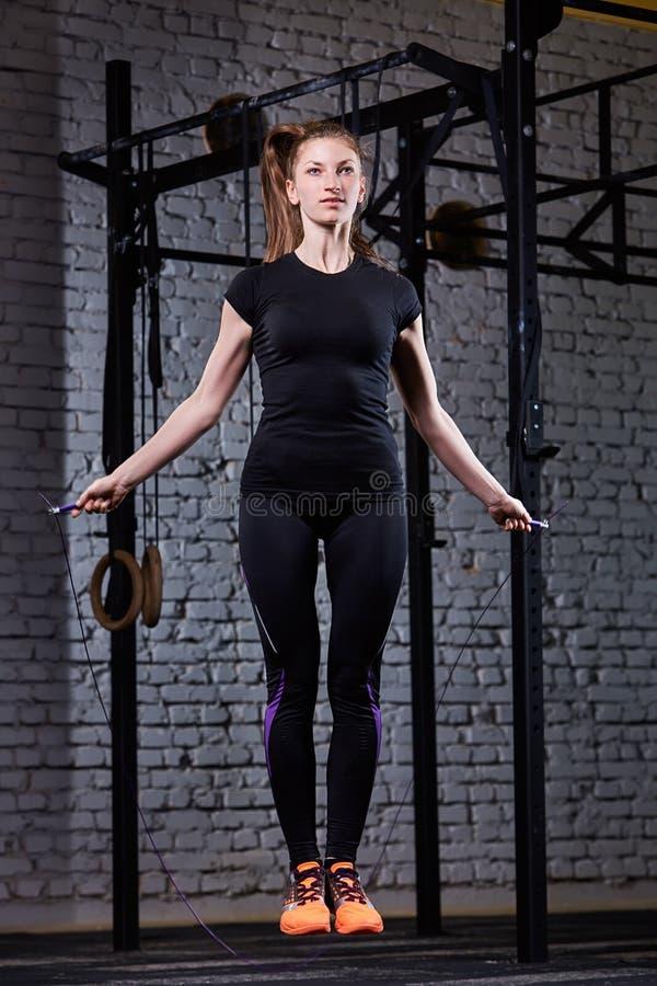 Giovane bella donna sportiva che lavora con la corda di salto nella palestra adatta dell'incrocio contro il muro di mattoni fotografia stock