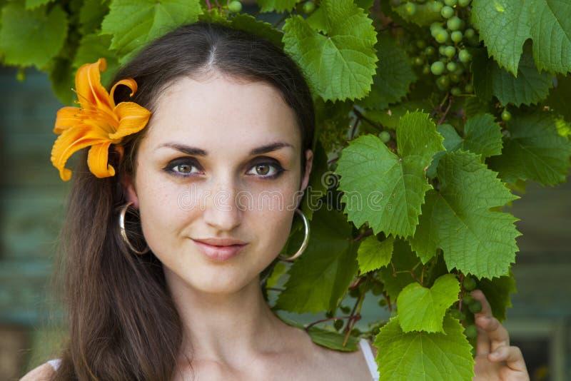 Giovane bella donna sui precedenti dell'uva fotografie stock libere da diritti