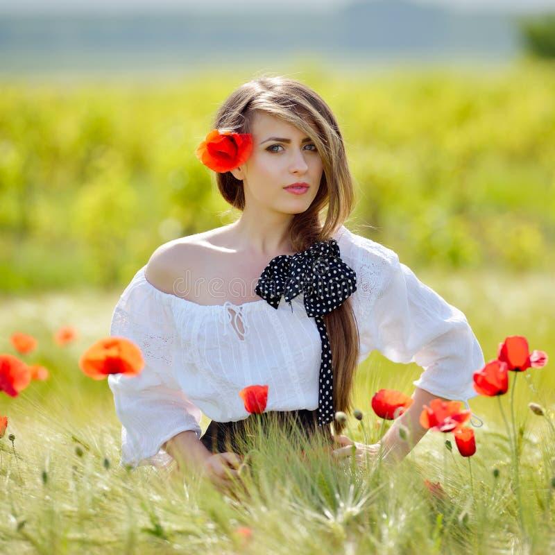 Giovane bella donna sul giacimento di cereale con i papaveri di estate fotografia stock libera da diritti