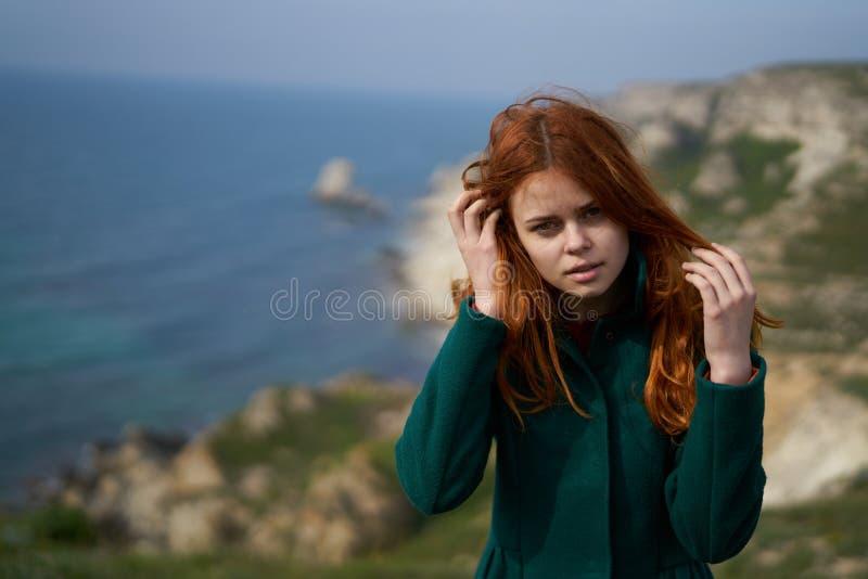Giovane bella donna sull'orlo di una scogliera vicino al mare fotografie stock libere da diritti