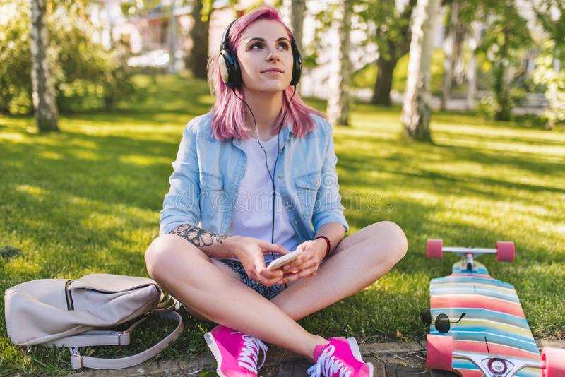 Giovane bella donna sveglia con capelli rosa in cuffie che ascolta la musica che sogna e che cerca sedentesi nel parco sull'erba  fotografia stock