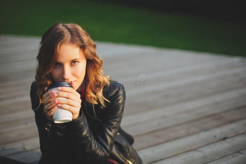 Giovane bella donna in un caffè bevente del rivestimento nero immagine stock libera da diritti
