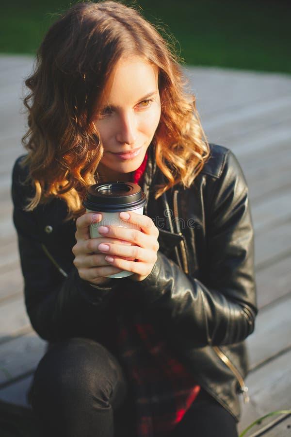 Giovane bella donna in un caffè bevente del rivestimento nero fotografia stock