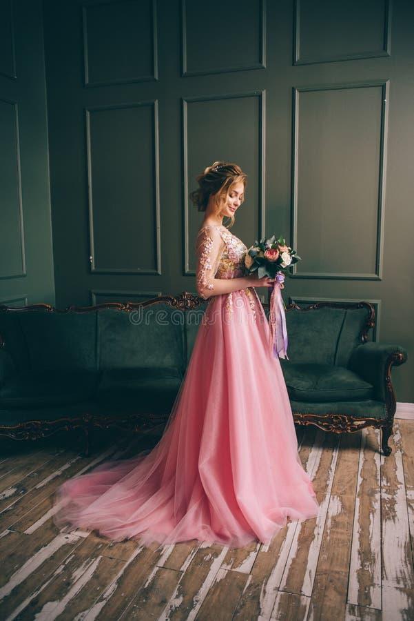 Giovane bella donna in un vestito rosa che sta in una stanza d'annata fotografia stock