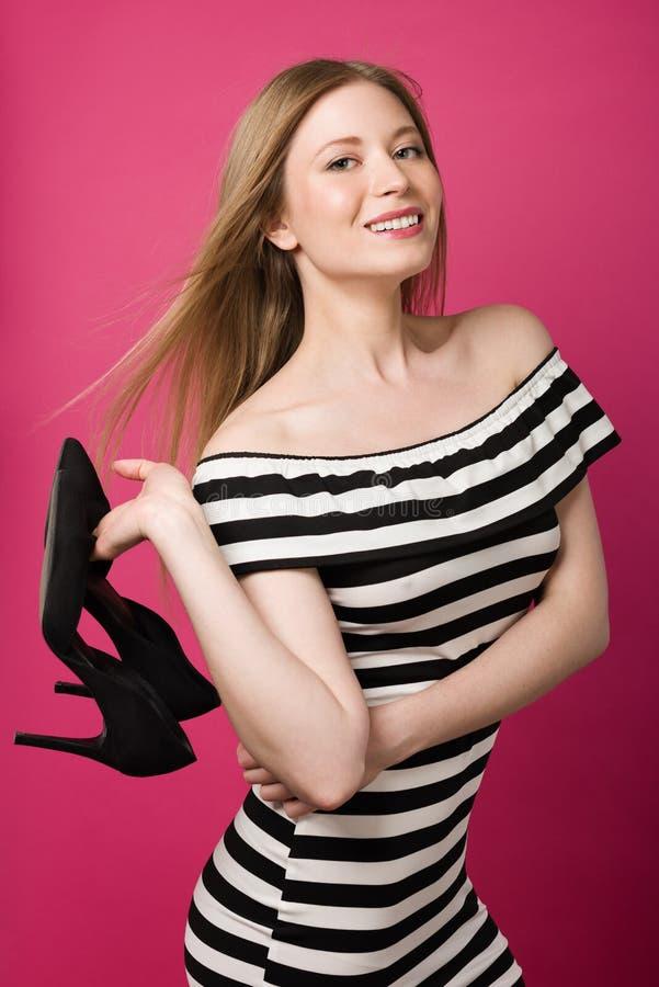 Giovane bella donna in un vestito, tenente le scarpe in sua mano Libertà e facilità fotografia stock libera da diritti