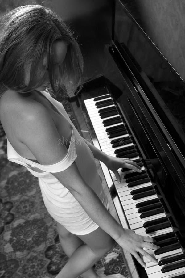 Giovane bella donna in una maglia che gioca il piano fotografie stock