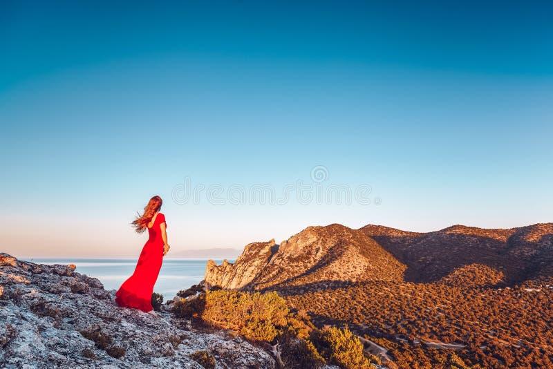 Giovane bella donna in vestito rosso che guarda al mare delle montagne immagini stock
