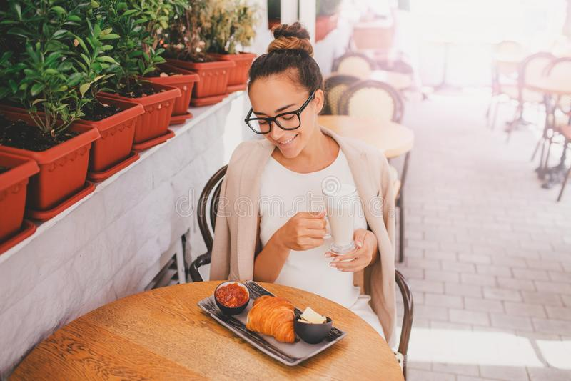 Giovane bella donna in vetri che mangiano prima colazione francese in caffè immagine stock