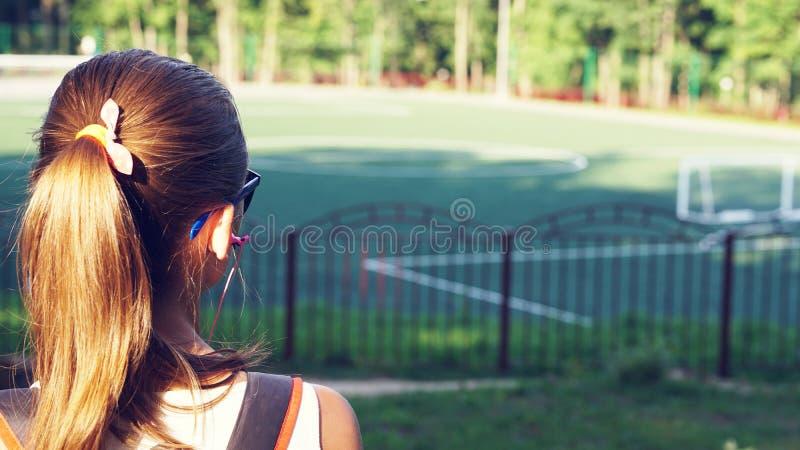 Giovane bella donna in vetri soleggiati allo stadio La ragazza guarda in avanti Vista dalla parte posteriore immagine stock