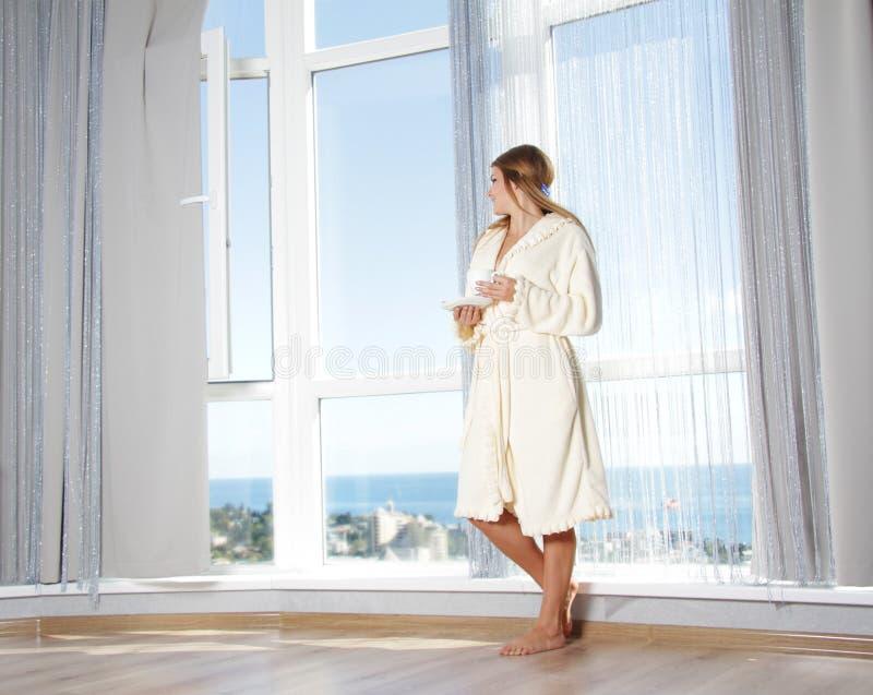 Giovane bella donna vicino alla grande finestra fotografie stock libere da diritti