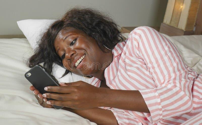 Giovane bella e donna afroamericana nera felice nella menzogne dei pigiami rilassata sulla rete del letto con il telefono cellula fotografia stock libera da diritti
