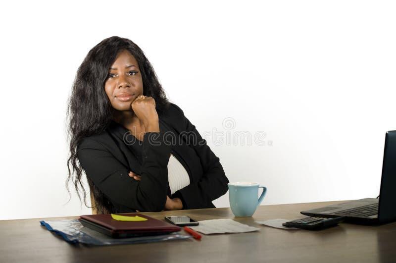 Giovane bella e donna di affari afroamericana nera sicura che lavora allo scrittorio del computer di ufficio che sembra comandone immagine stock