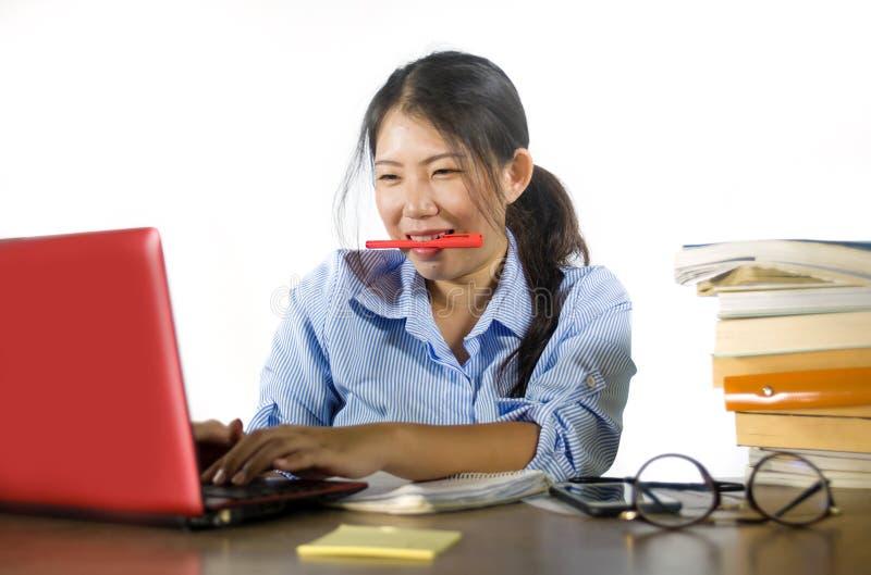 Giovane bella e ragazza cinese asiatica efficiente felice dello studente che lavora al progetto con seduta sicura sorridente del  fotografie stock