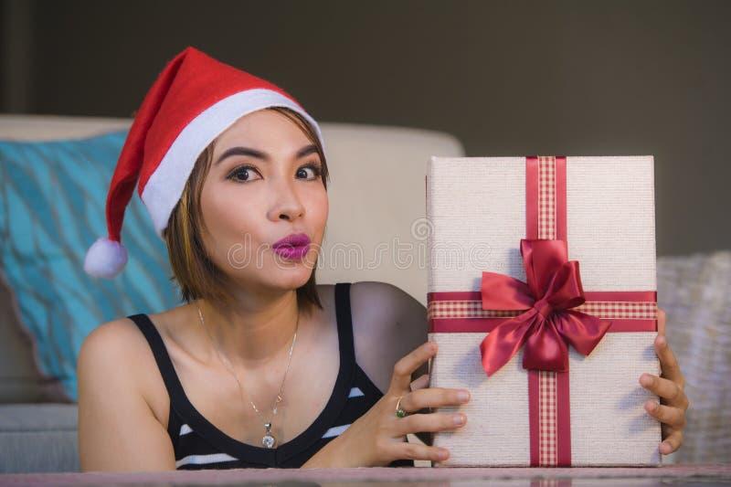 Giovane bella e ragazza felice in cappello di Santa che tiene la scatola del regalo di Natale con il nastro che sorride a casa st fotografia stock