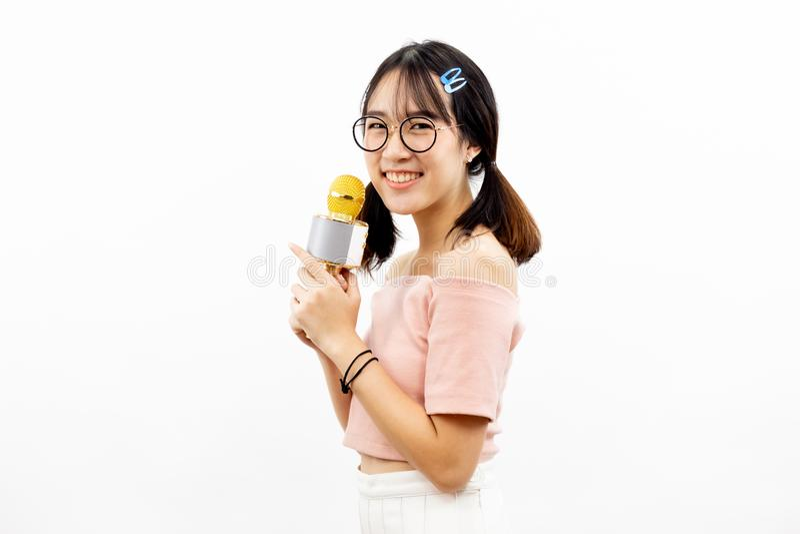 Giovane bella e studentessa abbastanza asiatica che tiene un microfono che canta con il sorriso attraente isolato sopra fondo bia fotografie stock