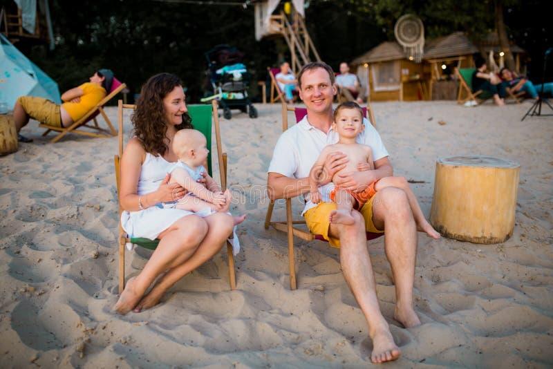 Giovane bella famiglia di quattro felice caucasica che si siede insieme abbraccio al caff? della spiaggia nel tramonto di sera Va fotografie stock