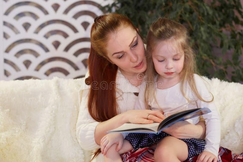 Giovane bella madre con la sua piccola figlia che legge un libro che si siede sullo strato fotografia stock libera da diritti