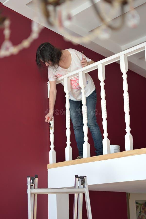 Giovane bella pittura della donna un ballustrade del bordo bianco con una spazzola fotografie stock