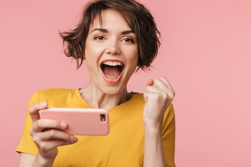 Giovane bella posa felice della donna isolata sopra il fondo rosa della parete per giocare dal telefono cellulare immagine stock libera da diritti