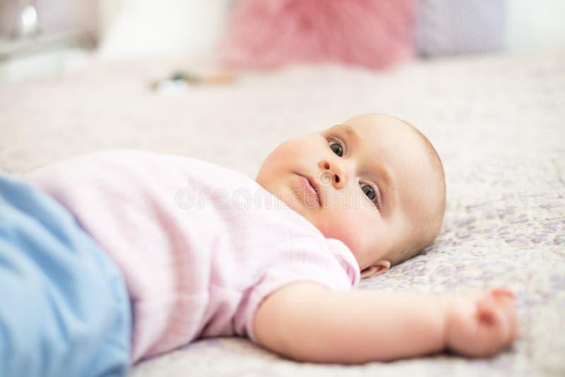 Giovane bella, ragazza adorabile che si trova su un letto con fondo bianco Il genitore ed il bambino sono ridenti e giocanti insi fotografie stock