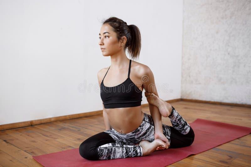 Giovane bella ragazza atletica che pratica i asanas dell'interno di yoga Preparando a re monco di una gamba Pigeon, Eka Pada fotografie stock