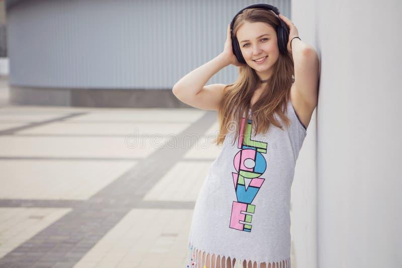 Giovane bella ragazza bionda dei pantaloni a vita bassa il giorno di estate divertendosi dentro immagine stock
