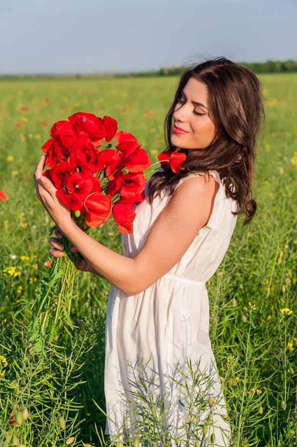 Giovane bella ragazza calma che sogna su un campo del papavero, estate all'aperto fotografia stock