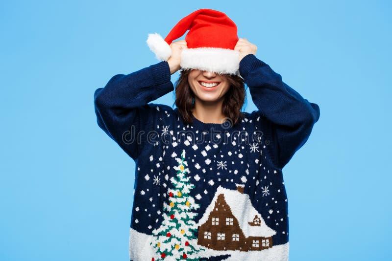 Giovane bella ragazza castana in cappello knited di natale e del maglione che sorride sopra il fondo blu immagine stock libera da diritti