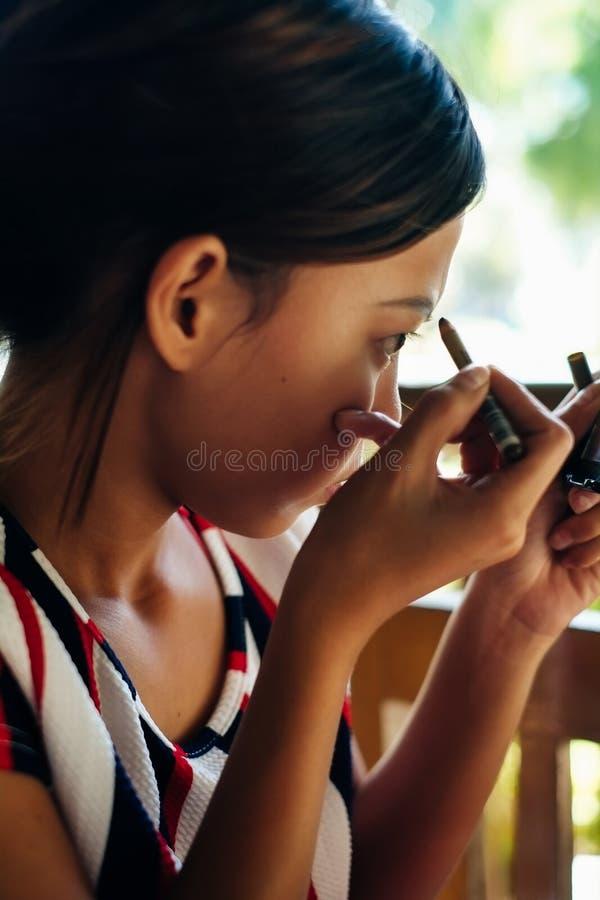 Giovane bella ragazza che applica trucco Sopracciglia di coloritura della ragazza con la fodera del sopracciglio immagini stock