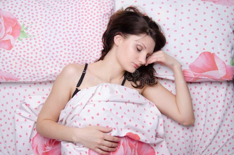 Giovane bella ragazza che dorme da solo a letto immagini stock