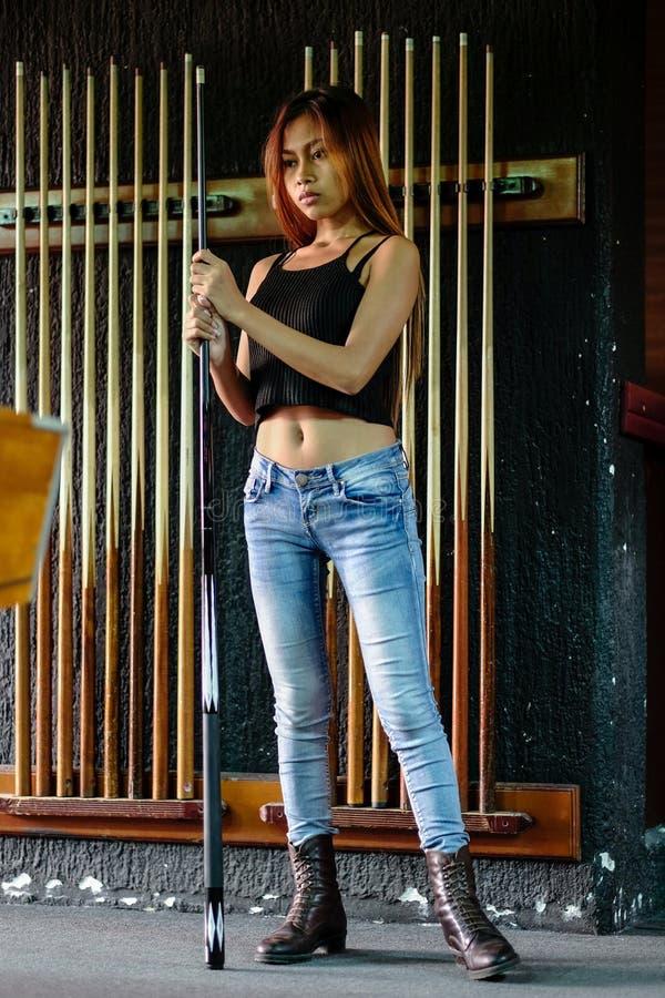 Giovane bella ragazza che gioca biliardo in un club immagini stock libere da diritti