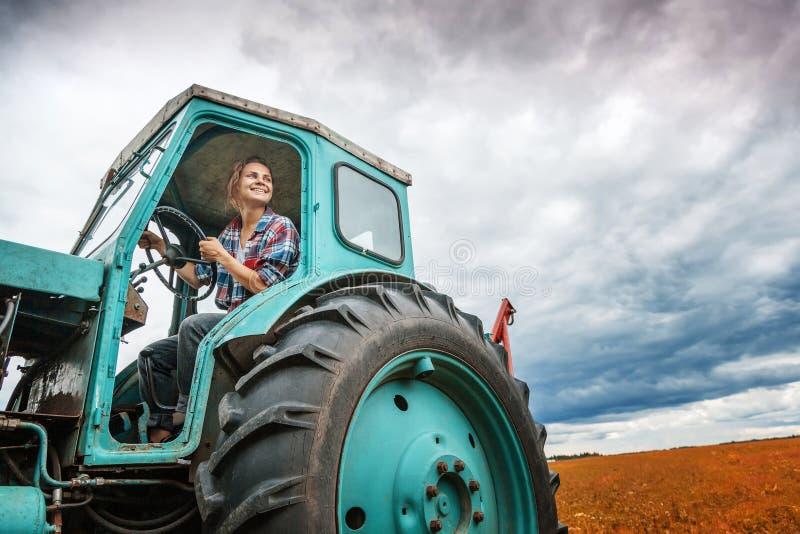 Giovane bella ragazza che lavora ad un trattore nel campo, insolito immagini stock