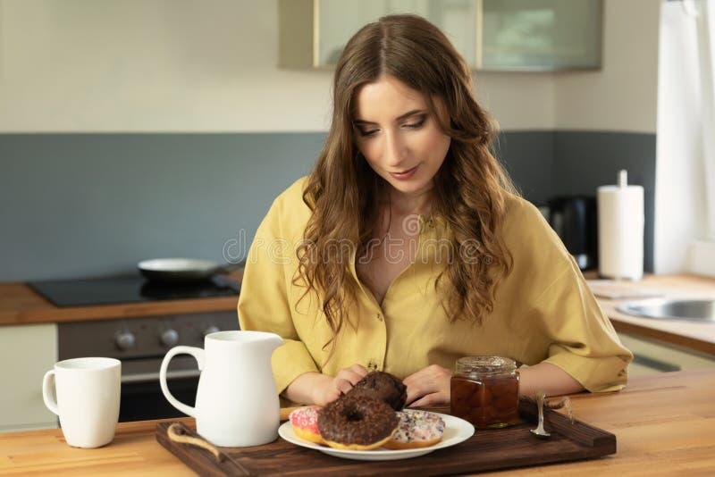 Giovane bella ragazza che mangia prima colazione a casa nella cucina fotografie stock libere da diritti