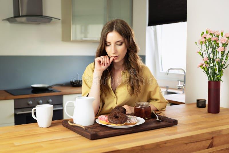 Giovane bella ragazza che mangia prima colazione a casa nella cucina fotografie stock