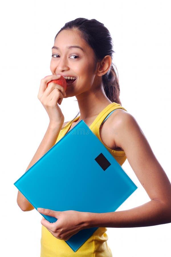 Giovane bella ragazza che mangia una mela e che tiene le scale fotografia stock