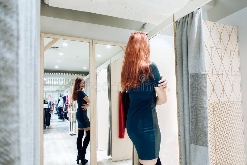 Giovane bella ragazza che prova sul nuovo vestito verde nella stanza adatta in boutique fotografia stock libera da diritti