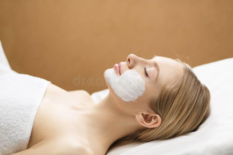 Giovane bella ragazza che riceve maschera facciale rosa nel salone di bellezza della stazione termale fotografia stock