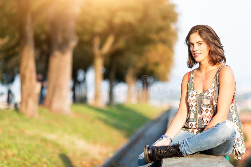 Giovane bella ragazza che si siede su una parete bassa in un parco nella città immagini stock libere da diritti