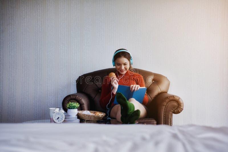 Giovane bella ragazza che si siede sul sofà per colto un libro e una prima colazione nella stanza leggera Festa di distensione immagini stock libere da diritti