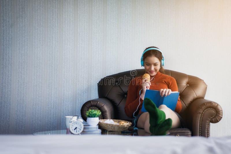 Giovane bella ragazza che si siede sul sofà per colto un libro e una prima colazione nella stanza leggera Festa di distensione immagini stock