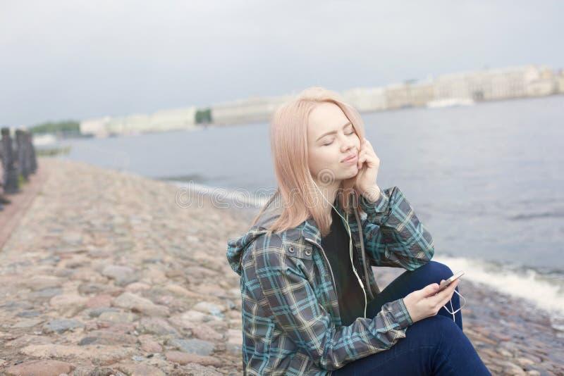 Giovane bella ragazza che si siede sulla spiaggia e che ascolta la musica sul vostro smartphone Sta riposando e pensando fotografia stock libera da diritti