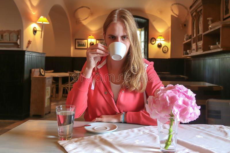 Giovane bella ragazza che si siede in un caffè ed in un caffè bevente immagine stock libera da diritti