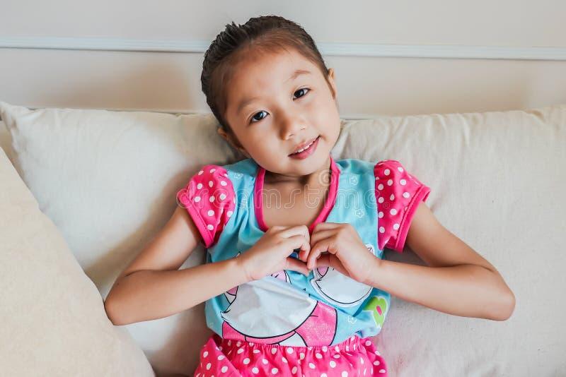 Giovane bella ragazza che sorride nell'amore che mostra simbolo e forma del cuore con le mani nella mia casa fotografia stock