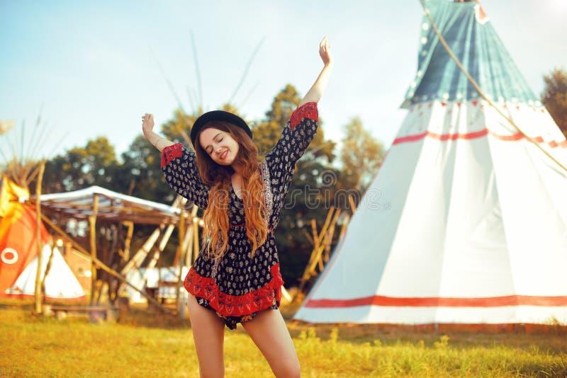 Giovane bella ragazza che sorride sul tepee del fondo, casa indiana indigena dei tipi Ragazza graziosa in cappello con cerly cape fotografie stock libere da diritti