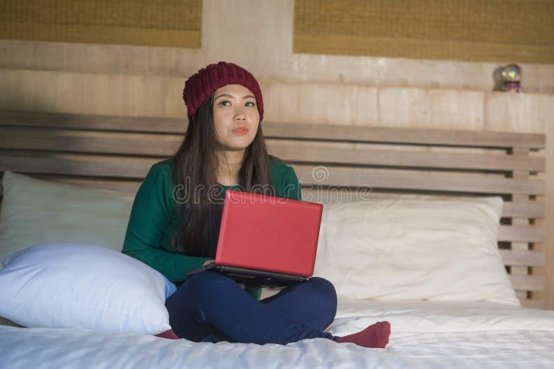 Giovane bella ragazza cinese asiatica felice nell'inverno fulgido rilassata sul letto facendo uso del soci godente premuroso e pe immagine stock