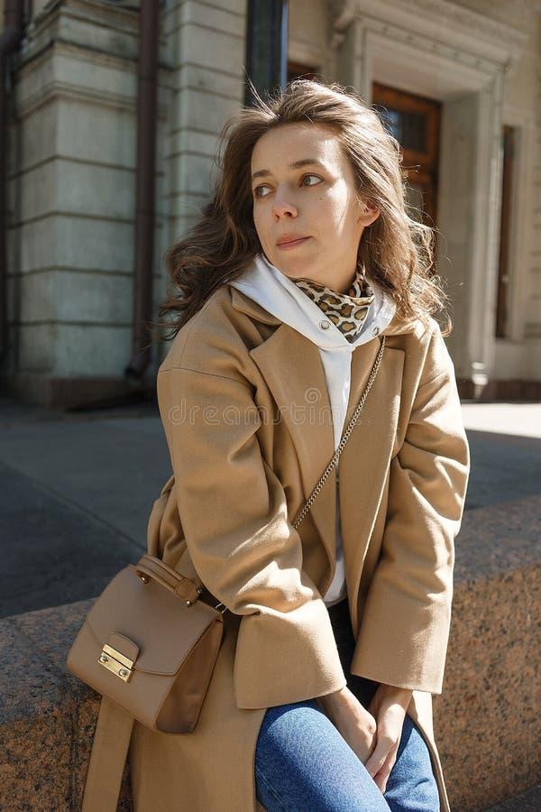 Giovane bella ragazza con capelli lunghi in cappotto beige un giorno soleggiato che si siede su un bordo e su un sorridere Ritrat immagine stock libera da diritti
