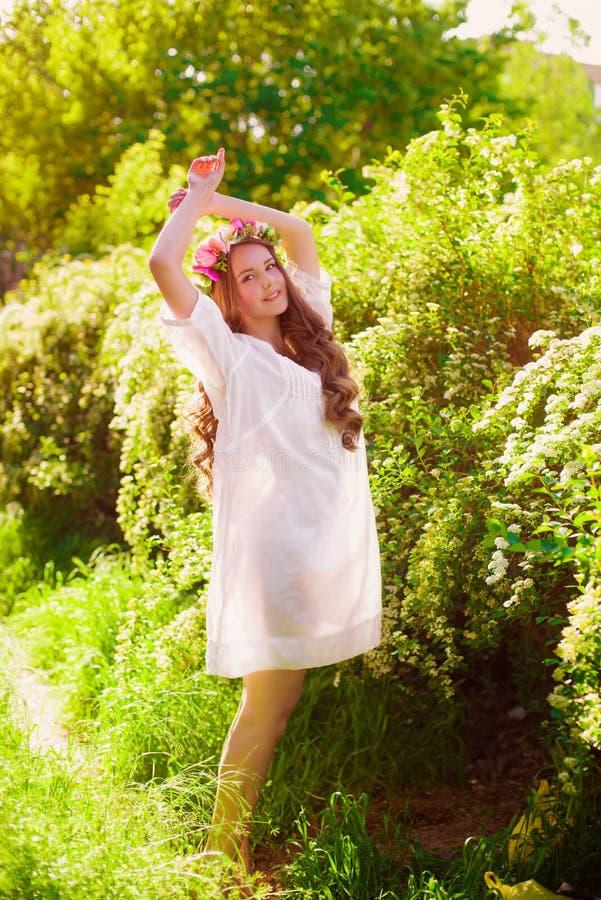 Giovane bella ragazza con capelli lunghi in corona floreale in primavera fotografie stock libere da diritti